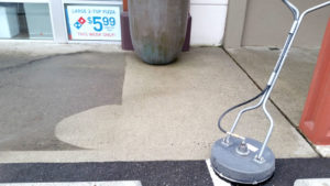 Power washing storefront concrete
